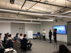 Students conduct a presentation in front of multiple students.