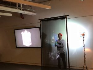 A student stands in front of a horizontal glass screen.