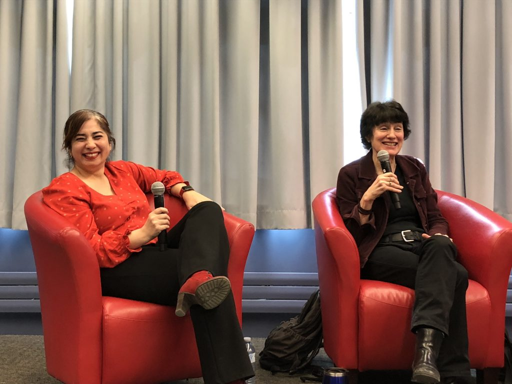 Two women sitting on red chairs with a microphone in their hand.